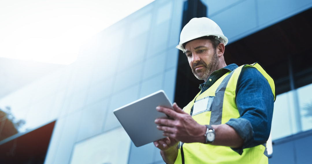 A construction worker using a tablet on site is slowed down by outdated technology.